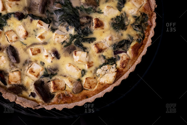 Overhead view of a spinach, feta and mushroom quiche