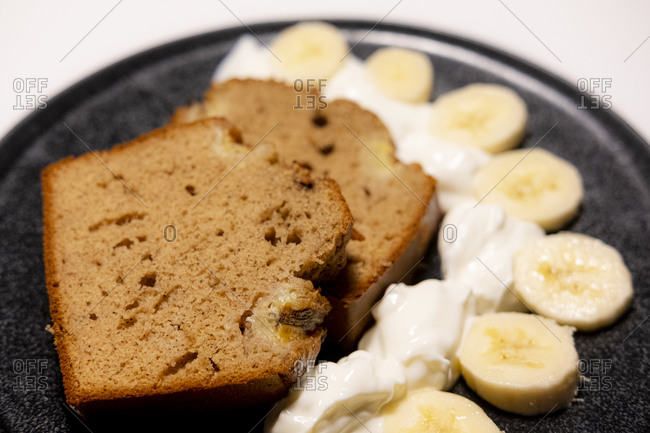 Slices of banana bread with Greek yogurt and banana on a black plate