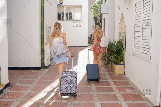 Two happy girls arriving at his holiday apartment carrying their suitcases. Rear view