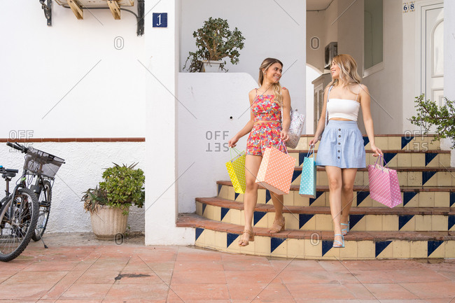Two happy blond girls coming out of a boutique with their shopping bags