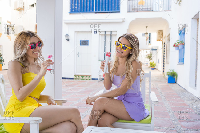 Happy female couple in yellow and purple dresses having ice cream on the terrace