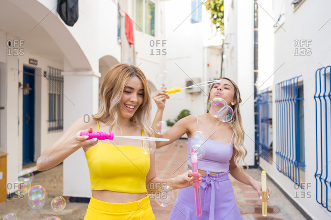 Two blond girls in purple and yellow dresses playing with soap bubbles in the street