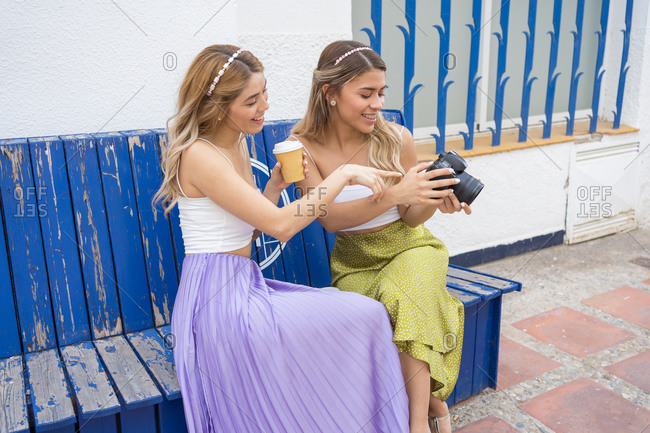 Two blonde girls look at the camera pictures while having a coffee sitting on a blue bench