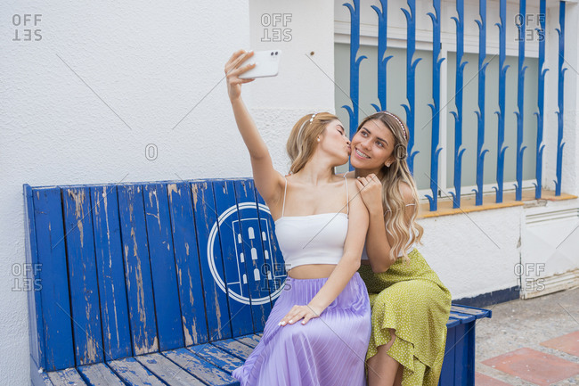 Two blonde girls take a self-portrait sitting on a blue bench while one kisses the other