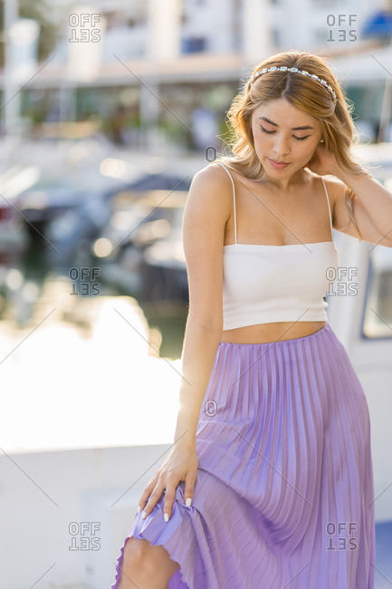Pensive girl with purple skirt and white top in the harbor