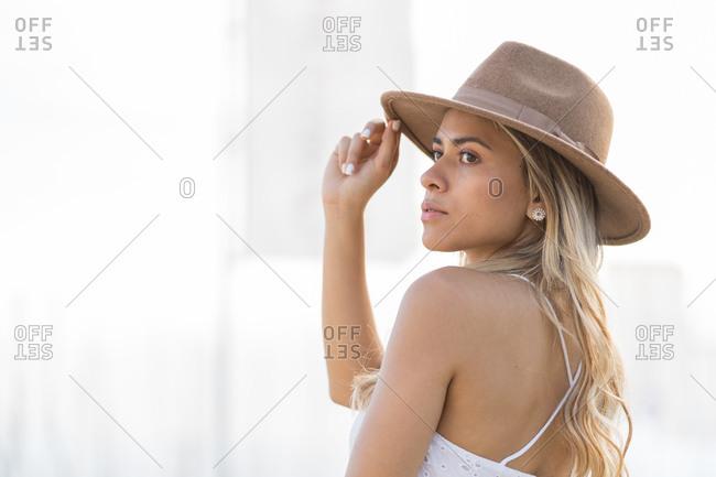 Elegant melancholic girl, facing the sea, touching her hat