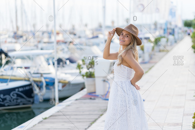 Attractive blonde woman with white dress and brown hat in harbor.
