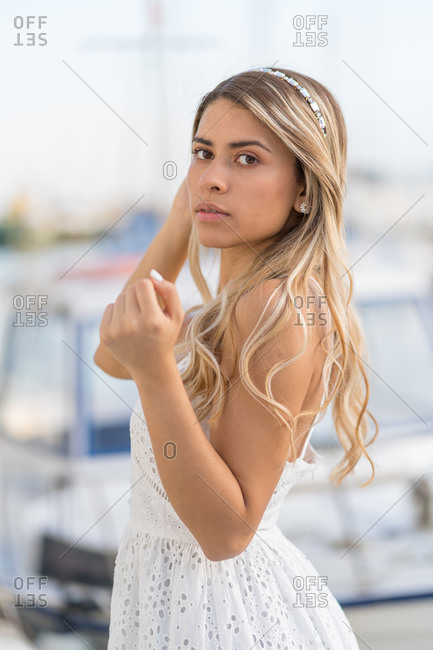 Attractive blonde woman with white dress in harbor.