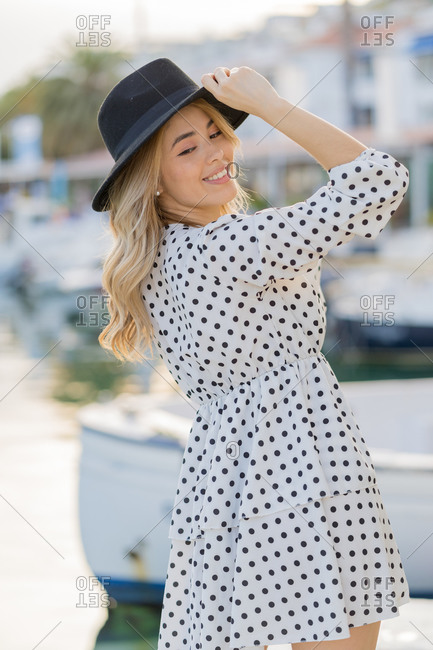 Elegant young blonde woman in white dress and black hat posing happily in the harbor