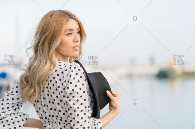 Elegant melancholic girl, facing the sea, wearing a white dress and a black hat