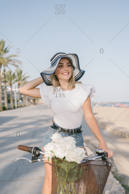 Pretty woman wearing hat and shorts riding her bicycle near the sea