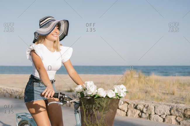 Happy young woman riding her bicycle in summer