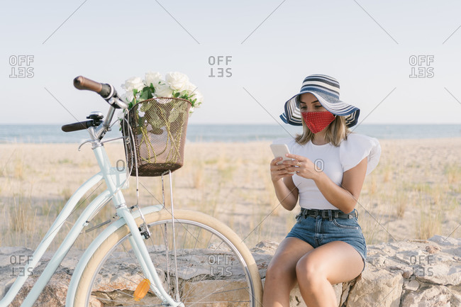 Young woman with a medical mask consulting her mobile phone while she is resting next to her bike on the promenade
