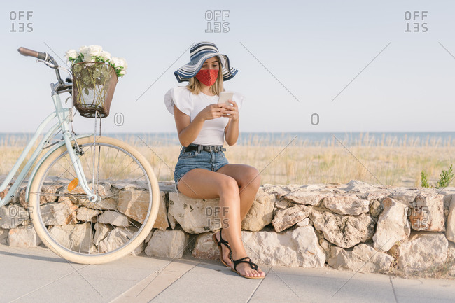 Young woman with a medical mask consulting her mobile phone while sitting by her bicycle on the promenade