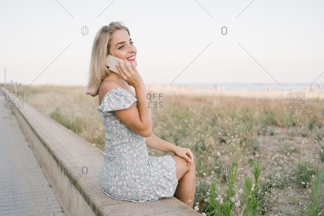 Happy woman talking on her cell phone while sitting on the promenade