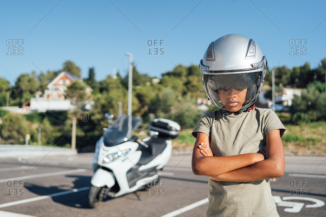 Afro boy with motorbike case posing seriously in front of his father's bike
