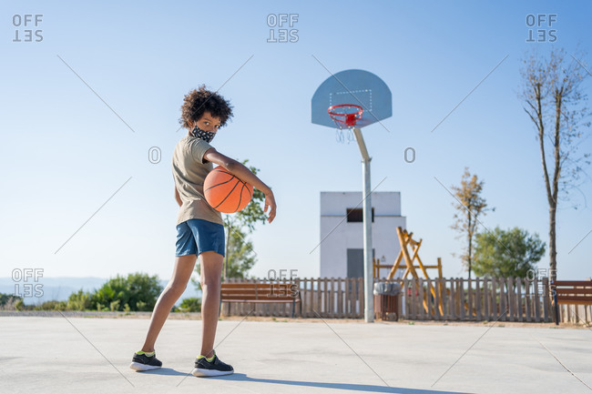 Afro boy wearing medical mask with a ball under his arm on an outdoor basketball court