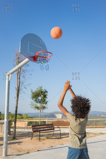African american boy throwing a ball in a basket on a basketball court. Rear view