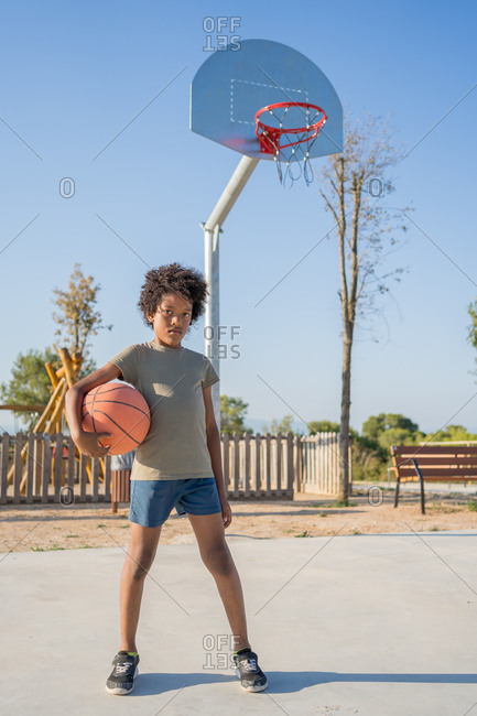 African american boy with a ball under his arm on an outdoor basketball court