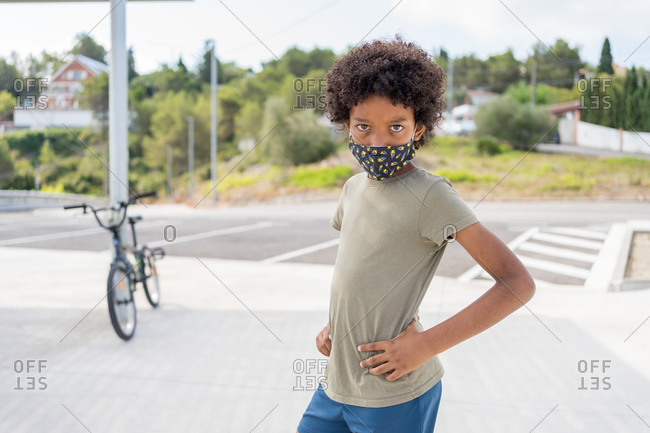African American boy with medical mask posing near his bicycle leaning against a street light