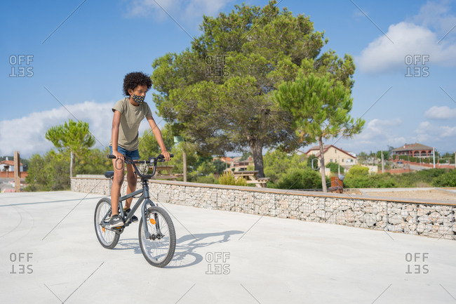 Afro american boy wearing face mask riding a bike outdoors