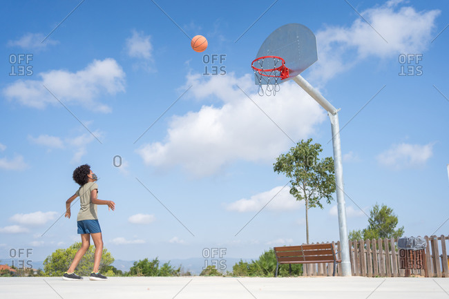 Afro american boy throwing a ball in a basket on a basketball court