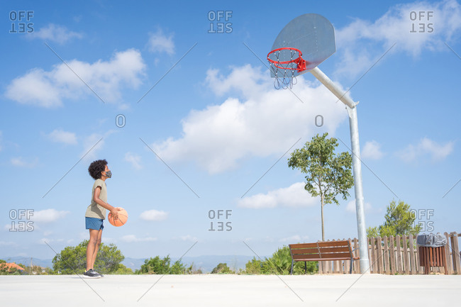 African american boy with medical mask concentrating before shooting a basket on an outside court