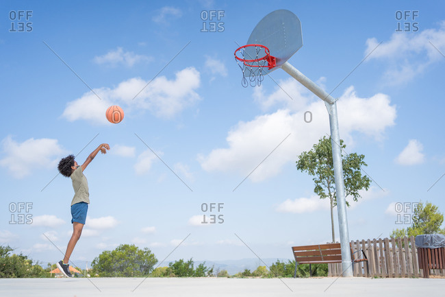 African american boy with medical mask throwing a ball in a basket on a basketball court
