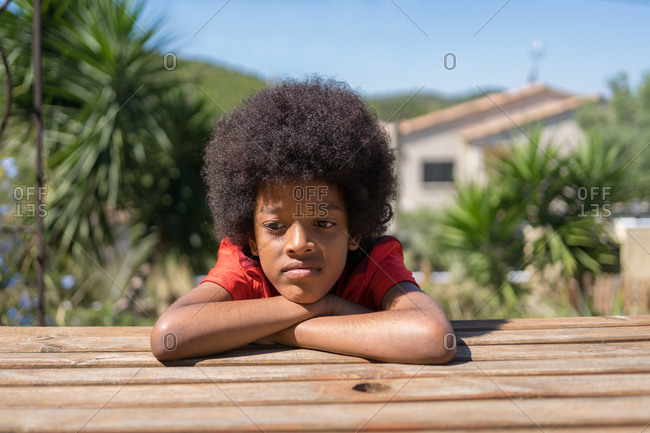 African-American boy wearing a red T-shirt is bored sitting on a bench in his backyard