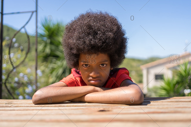 African-American boy wearing a red T-shirt is angry sitting on a bench in his backyard