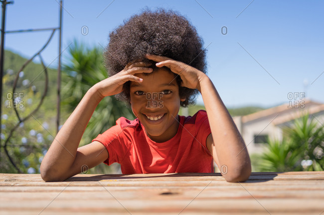 African-American boy wearing a red T-shirt is happy sitting on a bench in his backyard