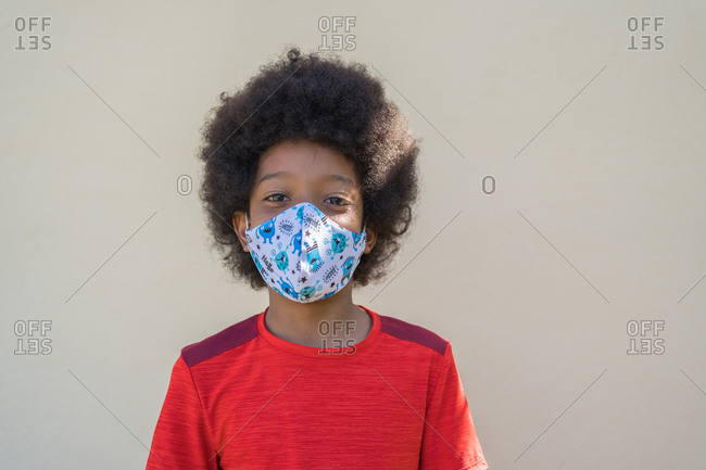 Happy African-American boy wearing a red T-shirt and a mask on a beige background