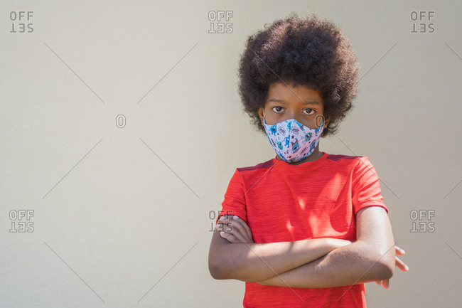 Angry African-American boy wearing a red T-shirt and a mask on a beige background