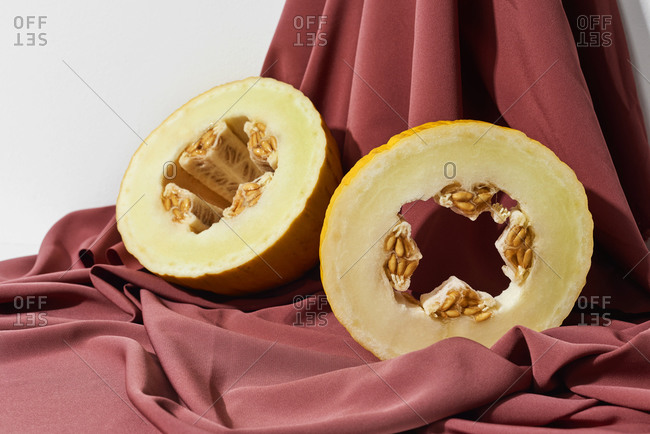 A halved canary melon on a maroon draped fabric background