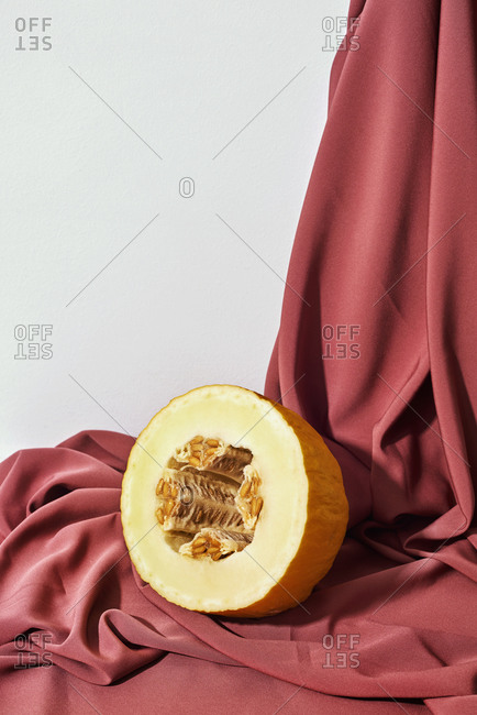 Half a canary melon on a maroon draped fabric background