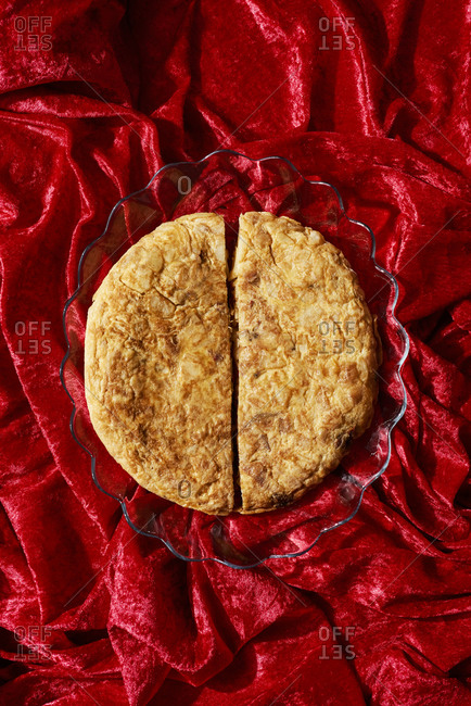 High angle view of a spanish omelette in a glass plate on a red draped fabric background