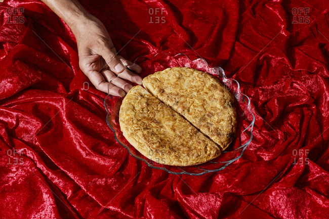 Closeup of a man holding a glass plate with a spanish omelette, against a red draped fabric background
