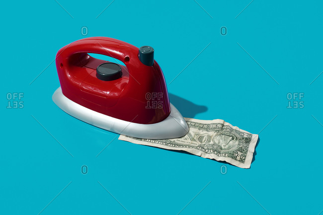 Ironing a dollar with a red iron on a blue background with some blank space