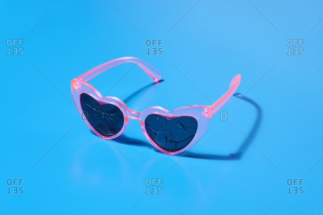 A pair of pink heart-shaped sunglasses, with broken glasses, on a blue background