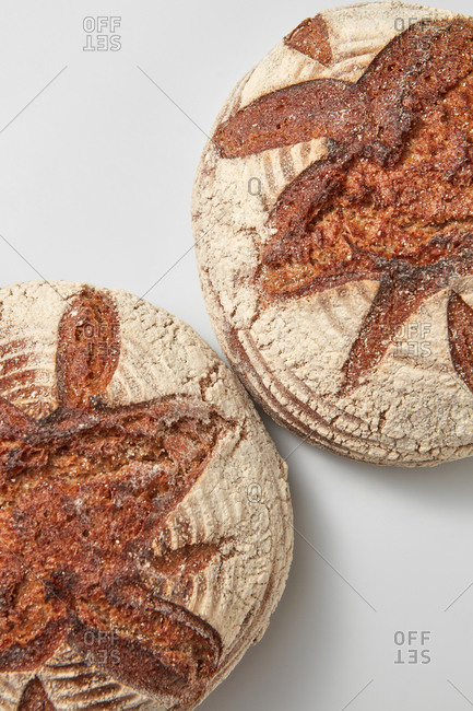 Homemade freshly baked wholegrain organic natural bread on a light grey background with soft shadows, copy space. Close up top view. Natural dieting food.