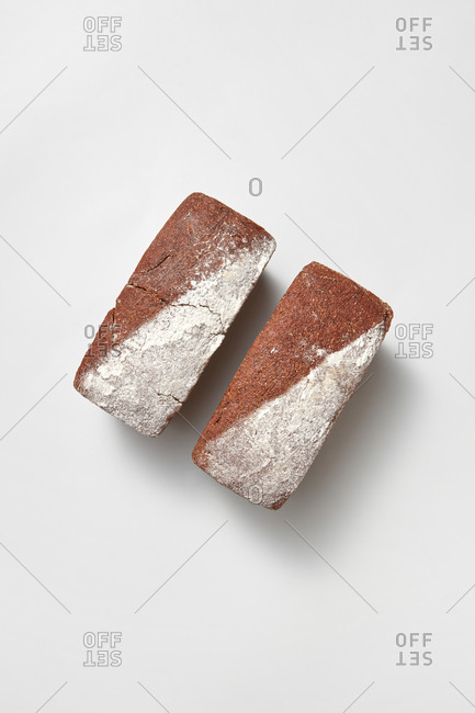 Top view two loaves of freshly baked homemade natural organic bread on a light grey background with soft shadows, copy space. Natural dieting food.