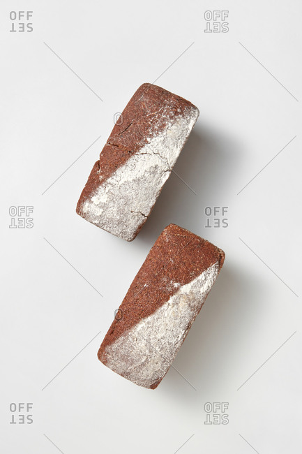 Top view two loaves of natural organic homemade freshly baked bread on a light grey background with soft shadows, copy space. Natural dieting food.