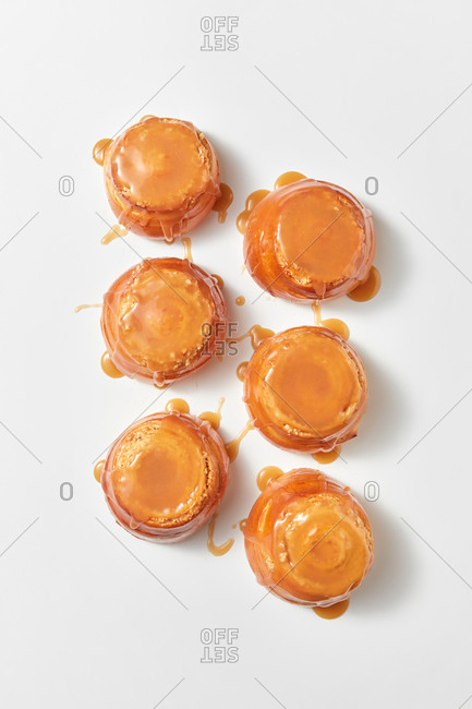 Delicious freshly baked homemade sweet delicious buns with caramel sauce, bakery pattern on a light grey background with soft shadows, copy space. Top view.