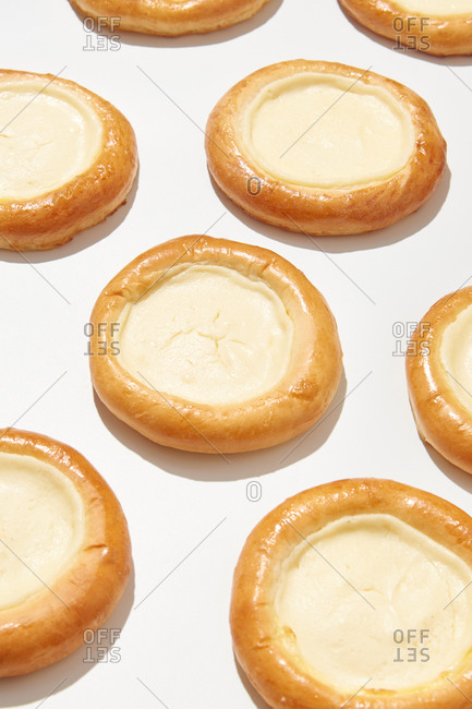 Freshly baked cheesecakes, vatrushka with delicious light cottage cheese cream on a light gray background with shadows, place for text. Close up view.