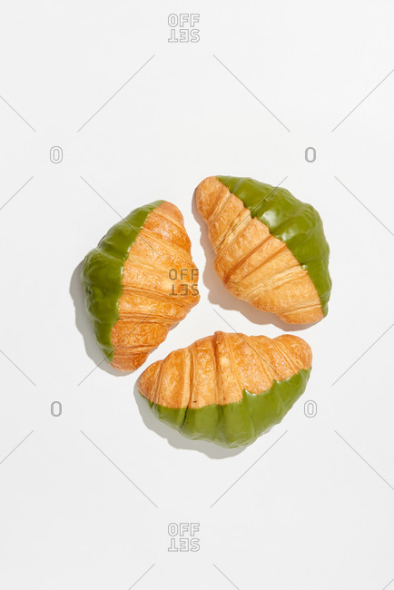 Fresh homemade delicious french croissants with green icing on a light gray background with hard shadows, copy space. Top view. Concept of breakfast continental.