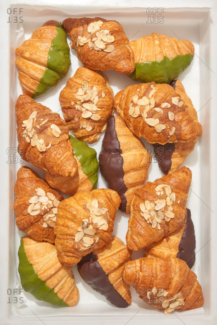 Mix from different freshly baked homemade croissants with almond, chocolate and green icing top in a box. Top view. Concept of breakfast continental.