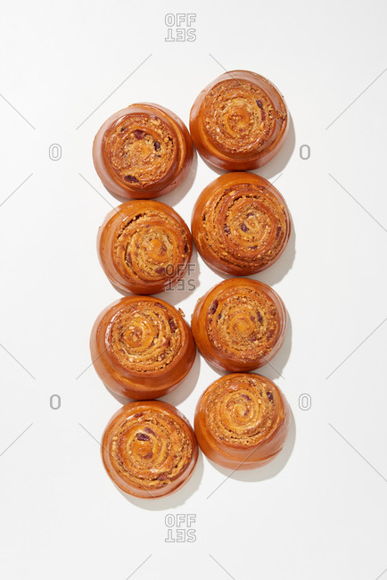Homemade freshly baked sweet delicious rolled buns with raisin and cinnamon on a white background, hard shadows, copy space. Top view.