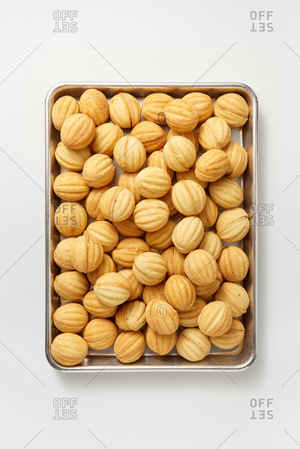 Tray with homemade delicious freshly baked cookies in the shape of walnuts on a light gray background, copy space. Top view.