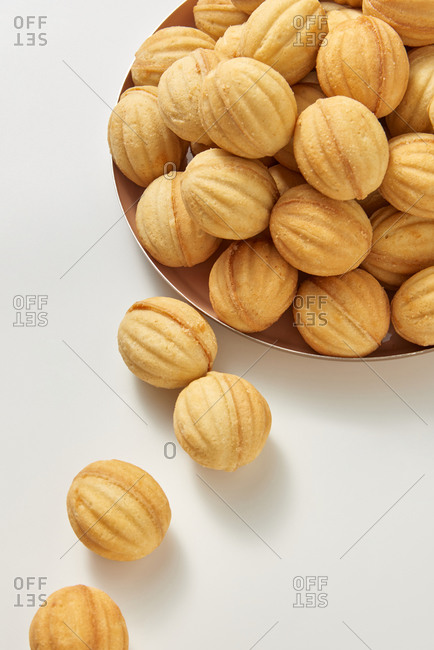 Ceramic plate with freshly baked homemade sweet dessert biscuits in the shape of walnuts on a light grey background with soft shadows, copy space. Top view.