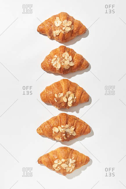 Delicious freshly baked french homemade croissants with almond crumbs on a light grey background with hard shadows, copy space. Top view. Concept of breakfast continental.